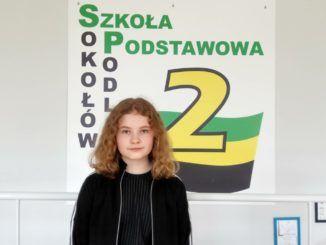 Zdjęcie laureatki konkursu na tle logo szkoły