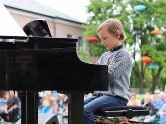 chłopak grający na fortepianie
